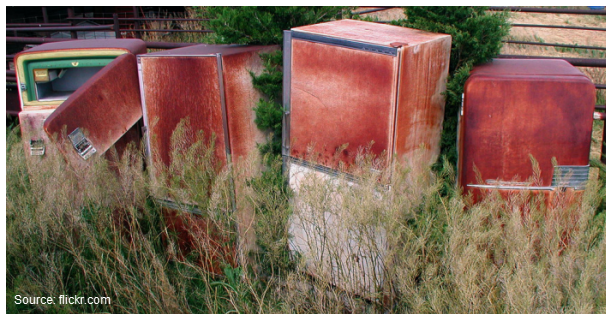 Stock photo of four abandoned red refrigerators