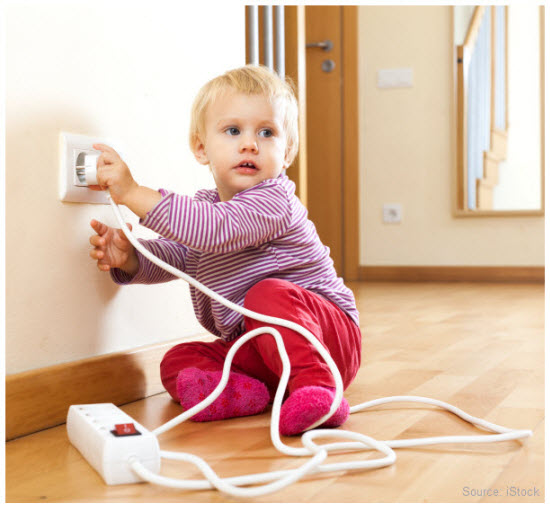 Stock imagery of a baby inserting a plug in a power outlet