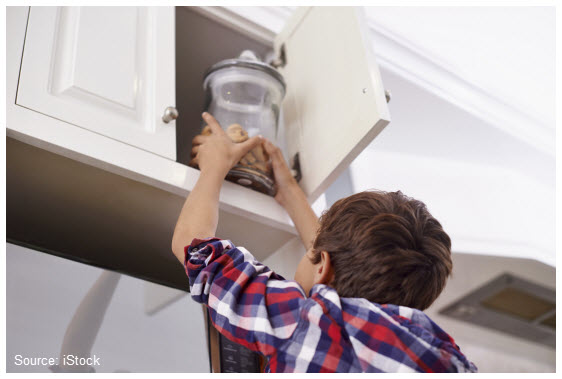 Stock photo of a little boy reaching for a cookie jar on a high shelf