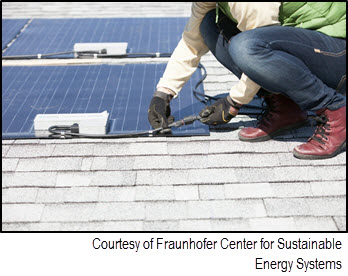 Photo of person installing solar PV panels on the roof of a house