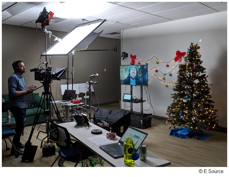 Still image of the set of the E Source holiday card, with remote employee Bryan Jungers on the screen